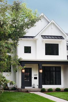 Modern Farmhouse House Tour White batten and board exterior with black porch columns, black windows and black metal roof Modern farmhouse White batten and board exterior White batten and board exterior