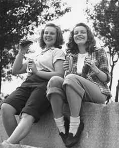 Two teenage girls drinking soda and eating hot dogs at Promontory Park in Chicago, Illinois, 1947. Photograph by Lil & Al Bloom.