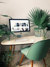 Tropical working space with modern designed table and chair with teal green and wood details. Light floor blends well with the natural tones.