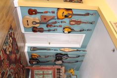 Musical instruments as wall art--plus, they are always easy to access. Used discounted coat hooks from Hobby Lobby and Gordman's (on sale for $1-$2 each) and one 20-pack of Dollar Tree pipe cleaners ($1, wrapped around tuning knobs of each instrument). Instrument hangers are usually $25-$75 each!