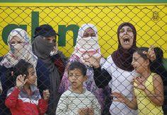 Vluchtelingen wachten in Hongarije naast de gestopte trein in Bicske.