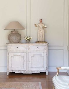 Katrin Cargill :: Interior Design.. Distressed white cabinet, naive figurine and fabulous stone lamp