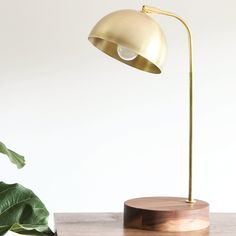 OVERVIEW A softly curving handcrafted lamp to brighten your space. Each large base is cut from a slab of thick wood, fitted with a polished brass arm and topped with a natural linen shade. DETAILS - O