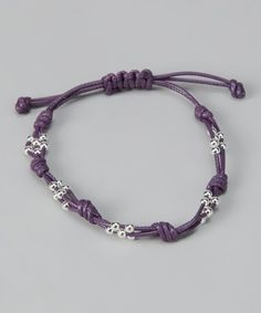 Bits of sterling silver glisten off of a richly colored cord to make one simply stunning bracelet. Adjustable ties make it easy to take off, but with such a versatile look that feature may not be necessary!