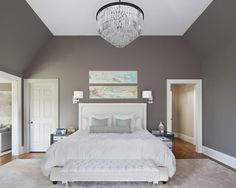 This sophisticated master bedroom features charcoal gray walls paired with pure white design accents, like the bed linens, platform bed and tufted bench. Mirrored nightstands sit on either side of the bed, while a glamorous chandelier hangs above the bed.