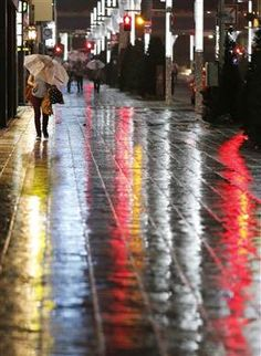 A woman struggles with strong winds and rain caused by Typhoon in Tokyo's Ginza Street, Japan|雨の銀座