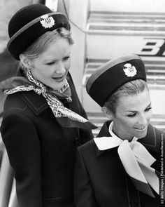 circa 1970: Two BEA air stewardesses fix their smiles in place, ready to greet a new planeload of passengers.