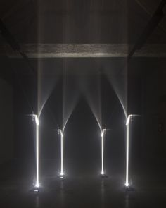 The Arcades installation is formed from 14 columns of light that shine upwards in thin bars before passing through fresnel lenses. The lenses refract the light in a series of graduating angles, creating the illusion of curving light.