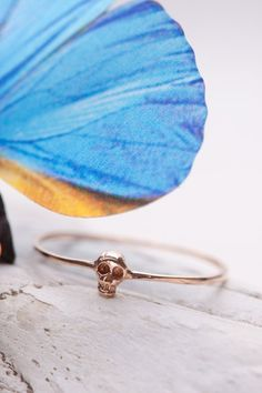 "14k tiny skully ring. Available in yellow or rose gold. Available in size 4-8.     Tiny skull measures about 3/16"" long. Image in the photo is enlarged. Please see product dimensions for a..."