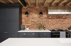 This industrial style shaker kitchen features exposed beams and contemporary brickwork as well as the latest cutting-edge appliances.
