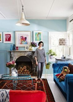 Paula Mills and Bella the Pugalier in the family's vibrant, art-filled lounge. The large painting over the fireplace is by Paula's friend Al...
