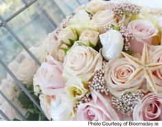 Fresh pink roses with seashells and starfish will look delicate and elegant - perfect for a beach wedding!