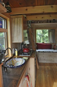 the sink in this tiny small space kitchen is gorgeous! And check out that window seat! Nice and deep and unusually comfy.   house
