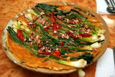 A plate of Dongnae pajeon, a Busan-style pancake made with whole scallions, sliced chili pepper, chopped seafood and wheat flour batter, served at a restaurant in [Gyeongju], North Gyeongsang province, South Korea It is usually eaten as an appetizer or snack in Korean cuisine  한국어: 대한민국 경상북도 경주시의 한 비빔쌈밥 식당에서 동래파전