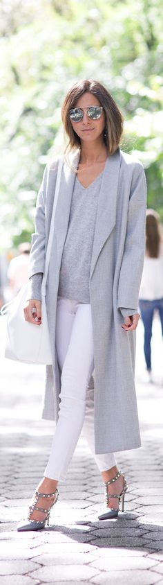 Arielle Nachami wears sophisticated grey coat with tight white trousers and statement heels.