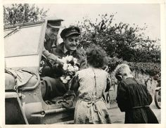 1944- French children present flowers to R.A.F. officers in Normandy, France.