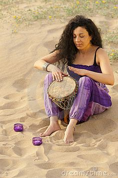 Djembe hand drum player in the sand... with candles...