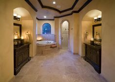 A Spanish-Mediterranean master bathroom with a dramatic vaulted ceiling features duel-arched vanities in a rich chocolate wood. Travertine tile is used for the floor. Mosaic tile trims the shower and elevated tub.