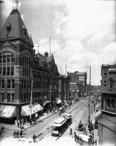 """View of Curtis Street from 16th (Sixteenth) Street in Denver, Denver County, Colorado. 1882- 1900. Shows the Tabor Grand Opera House, pedestrians, and a trolley car. Signs read: """"Teeth Filled Without Pain"""", """"F. E. Edbrooke & Co. Architects"""" """"Hodgson Architect"""" and """"Kirschner & Kirschner Architects"""". """"1880"""" and """"H.A.W. Tabor"""""""