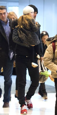 Jet-set: The designer's daughter Harper was seen in the arms of doting father David Beckham in New York on Tuesday as they made their way back to London following Victoria's successful NYFW showcase