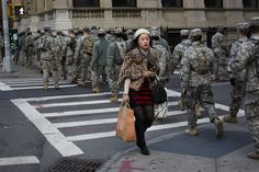 39)  A woman passes a group of National Guardsmen as they march up 1st Avenue towards the 69th Regiment Armory, on November 3, 2012, in New York. National Guardsmen remain in Manhattan as the city begins to move towards normalcy following Superstorm Sandy earlier in the week. (AP Photo/John Minchillo)