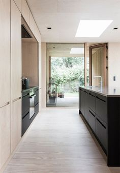 The cool black and light wood carpenter kitchen has discrete built-in closets and skylight windows.