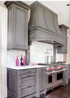 Grey kitchen cabinets and the commercial range. I freaking wish!!.