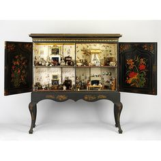 Antique dollhouse rooms inside a a cabinet [England, 1830-1839]
