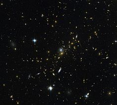 Galaxy clusters are some of the most massive structures that can be found in the Universe — large groups of galaxies bound together by gravity. This image from the NASA/ESA Hubble Space Telescope reveals one of these clusters, known as MACS J0454.1-0300. Each of the bright spots seen here is a galaxy, and each is home to many millions, or even billions, of stars.