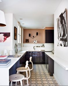 At Home in Paris featuring this gorgeous kitchen with open shelving, a patterned floor, black cabinets, and a white subway backsplash with Caroline Gayral on Natalie Catalina