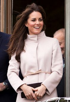Catherine, Duchess of Cambridge's hair is blown in the wind as she stands on the balcony of The Guildhall during first official visit to Cambridge