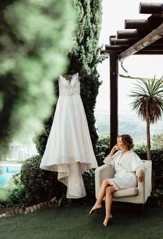 The bride is looking at her gown Villas, Got Married, One Shoulder Wedding Dress, Wedding Photos, White Dress, Gowns, Weddings, Bride, Wedding Dresses