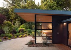 Dark cladding and flat roof are lovely and although this overhang for the patios is a little exaggerated we would want it to clear the doors at least.