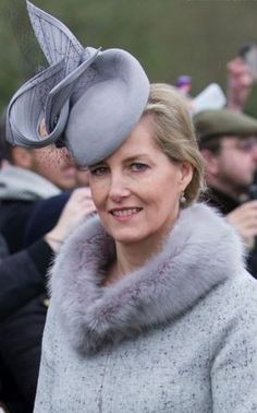 Countess of Wessex, December 25, 2015 in Jane Taylor | Royal Hats: Countess of Wessex looked wonderfully elegant in a grey tweed coat with matching hat. The cocktail hat, with a beret base, features a tall rim at the top of the hat. The small hat is given further visual punch with trimmings of a large twist of coordinating grey straw and a swath of black net tulle. Dove grey is an unexpectedly lovely color on Sophie and I thought she wore the piece well.