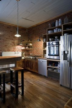 Kitchen with exposed brick walls, wood floors, stainless appliances, very urban chic