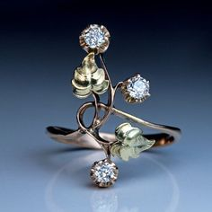 An Antique Art Nouveau Diamond Two-Color Gold Flower Ring, Moscow, 1899-1908. A 14K rose gold ring is designed as a stylized Art Nouveau flower with two chased green gold leaves and three sparkling old European cut diamonds.