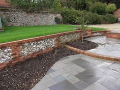 The walls retain the ground to provide a large flat lawn and different brick materials break up the view.