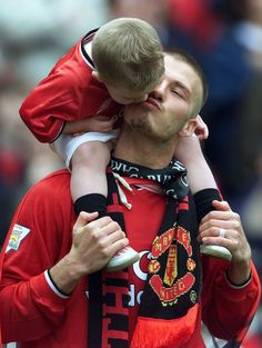 David Beckham gets a kiss from his son Brooklyn after winning the premiership in  Old Trafford Manchester May 5, 2001 | Reuters