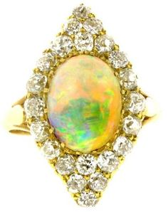 Antique opal and diamond cluster ring, circa 1900. Oval cabochon opal in a claw setting with an approximate weight of 2.50ct. In a marquise shaped diamond border set with twenty-two round old cut diamonds with an approximate weight of 1.50ct.