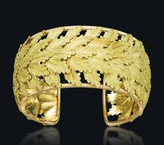 A GOLD BANGLE, BY BUCCELLATI   The openwork cuff designed as a series of overlapping textured gold leaves, circa 1960, 5.7 cm inner diameter, in navy blue fabric Mario Buccellati fitted case  Signed M. Buccellati