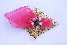 Broche flor cristal swarovski y cristal normal tonos rosa, champán y blanco. Lazada flor organdí fucsia. Montado sobre base rombo dorada motivo de 8x5 cm. REF.009