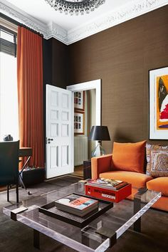 A modern chocolate brown living room idea with modern glass lighting and orange chairs and curtains. Modern living room ideas and furniture.