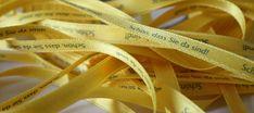 Hier sehen Sie ein schmales 6 mm breites Satinband in gelb mit einem Sinnspruch bedruckt Yellow