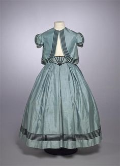 Child's dress consisting of skirt, bolero, belt and bow of blue silk decorated with narrow velvet bands. C. 1865-67. Gemeentemuseum Den Haag. Via Modemuze.