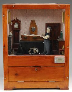 """John Dennison Coin-Operated Funeral Parlor Scene. Approx. circa 1885 - 1915, England. """"The scene depicts a man in his coffin at a funeral parlor. When a coin is inserted into the mechanism, a skeleton head appears behind the coffin, the corpse bolts to an upright position and turns his head. Then, the skull disappears and a devil appears."""""""