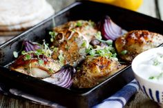 Greek Chicken Bake with Tzatziki - Serves 4-6    8 plump, free range chicken thighs  1 head of garlic, halved  2 red onions, cut into wedges  100g (3.53 ounces) Calamata olives  olive oil, to drizzle  2 tsp dried oregano  salt & pepper to taste  juice of 1 lemon  to serve