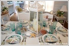 This table setting theme is all about the beach! She used seashells, candles, and a gorgeous lantern for her table centerpiece idea. Craft stores like Hobby Lobby carry seashells, starfish, cheap beach decor, as well as rope netting, and colored glasses.
