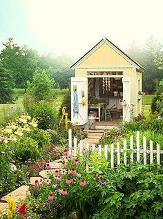 Adorable yellow potting shed surrounded by beautiful flowers! Heaven.