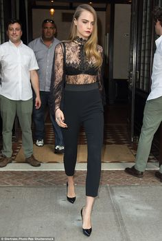 Showing some skin: Cara Delevingne showed off her trim figure in a sheer blouse and fitted...