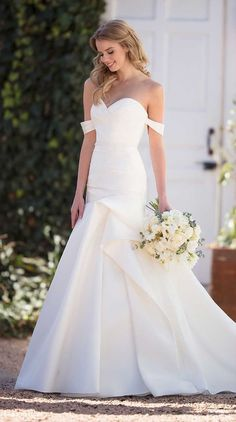 A unique style that mixes modern detailing with a traditional silhouette, turn heads in this silk wedding dress with ruching from Martina Liana. A completely-structured style, the neckline of this silk Zibeline gown is ruched and highlighted on either side with drapey, off-the-shoulder straps. From the waist, the fit-and-flare silhouette extends to the ground, featuring asymmetrical ruching that extends around to the back of the gown.